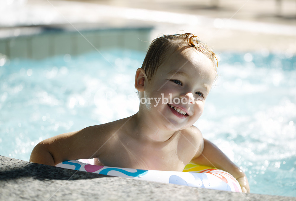 Kid learns to swim using a plastic water ring