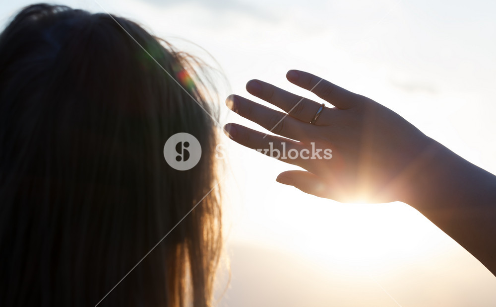 Woman hiding from the sun with hand