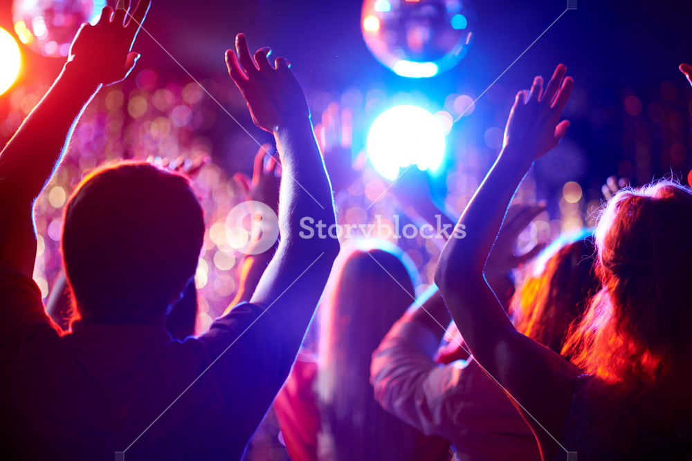 Crowd Of People With Raised Arms Dancing In Night Club