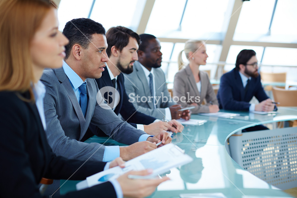 Row Of Business People Listening To Presentation At Seminar With Focus On Elegant Young Man