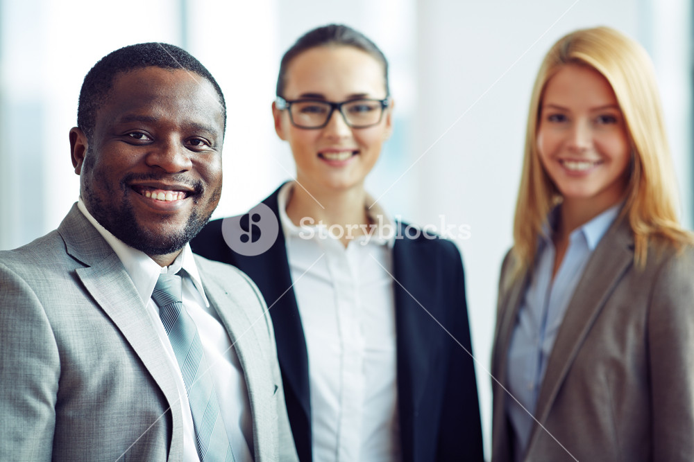 Smiling And Confident Businessman With Two Female Colleagues On Background