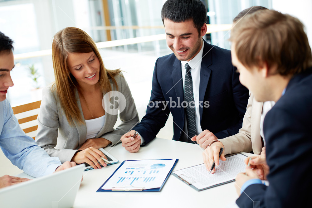 Image Of Business Partners Discussing Documents At Meeting