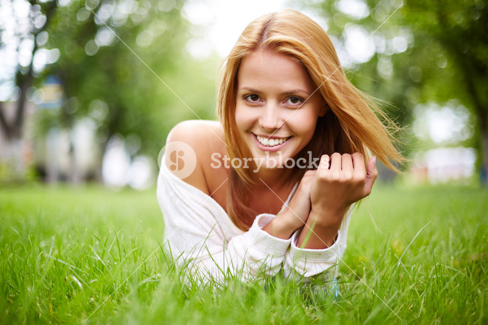 Happy Girl Lying In Grass And Looking At Camera With Smile