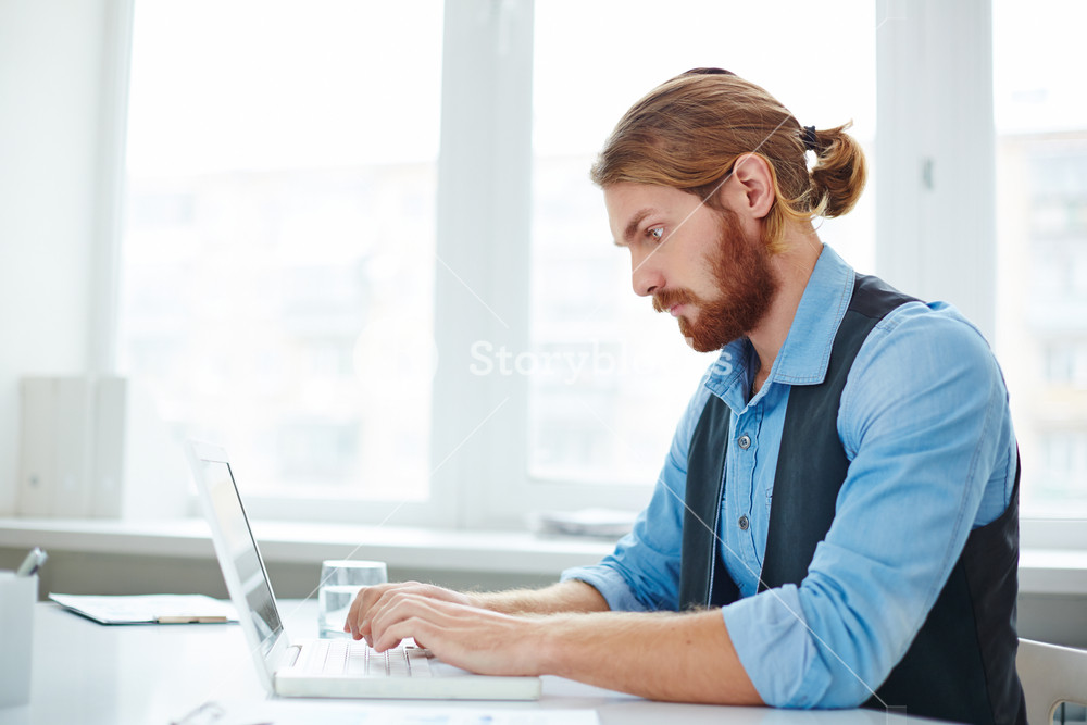 Serious Businessman Typing On Laptop At Workplace