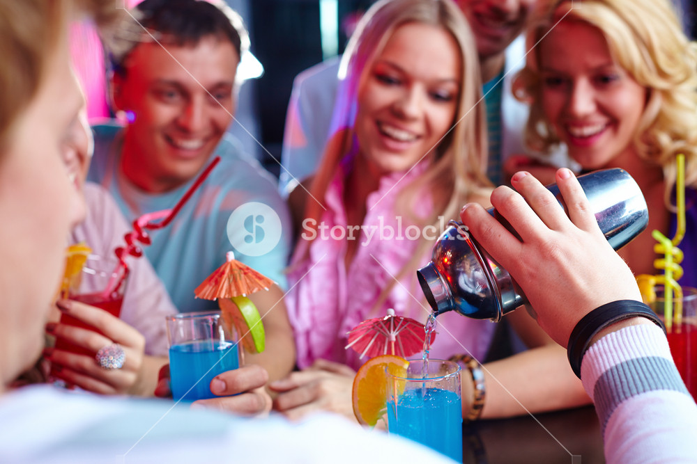 Photo Of Barman Hand Holding Bottle And Pouring Water Out Of It