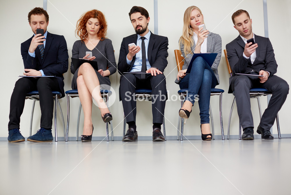 Row Of Several Business Partners Using Mobile Phones