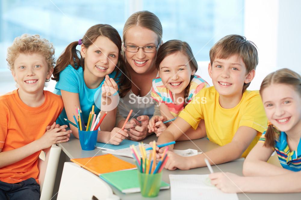 Portrait Of Joyful Schoolkids And Successful Teacher Looking At Camera