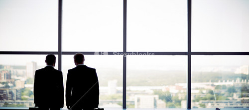 Silhouettes Of Two Businessmen Standing By The Window