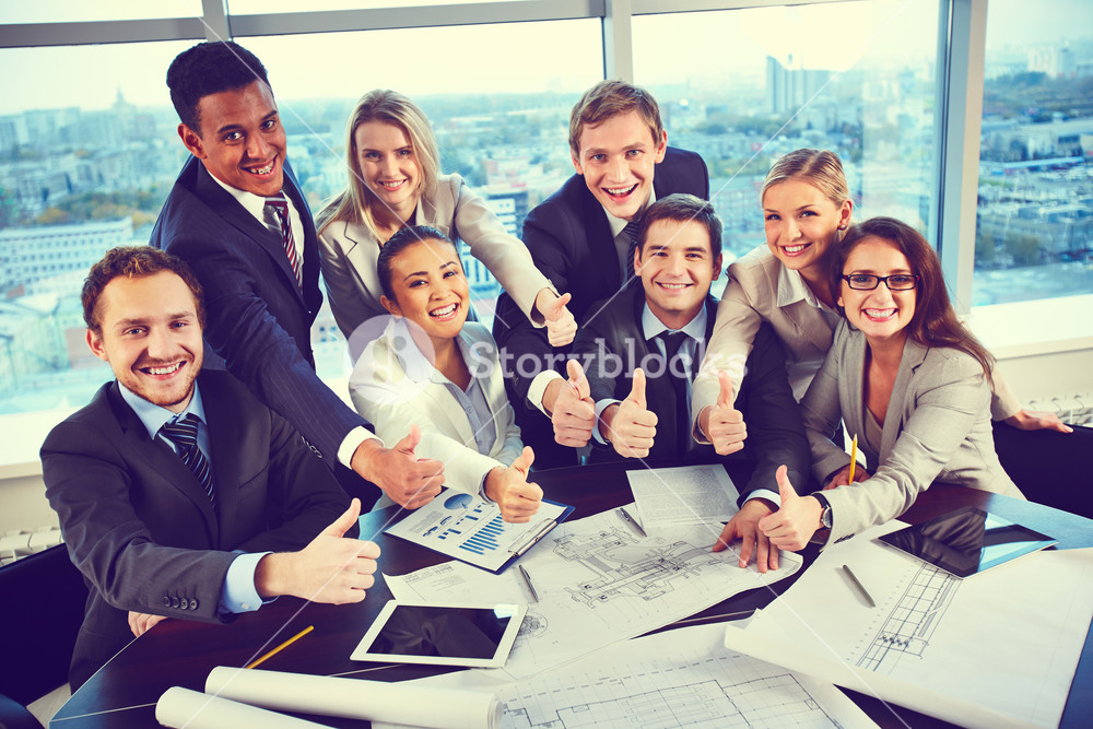Group Of Business Partners Showing Thumbs Up While Sitting At Workplace In Office