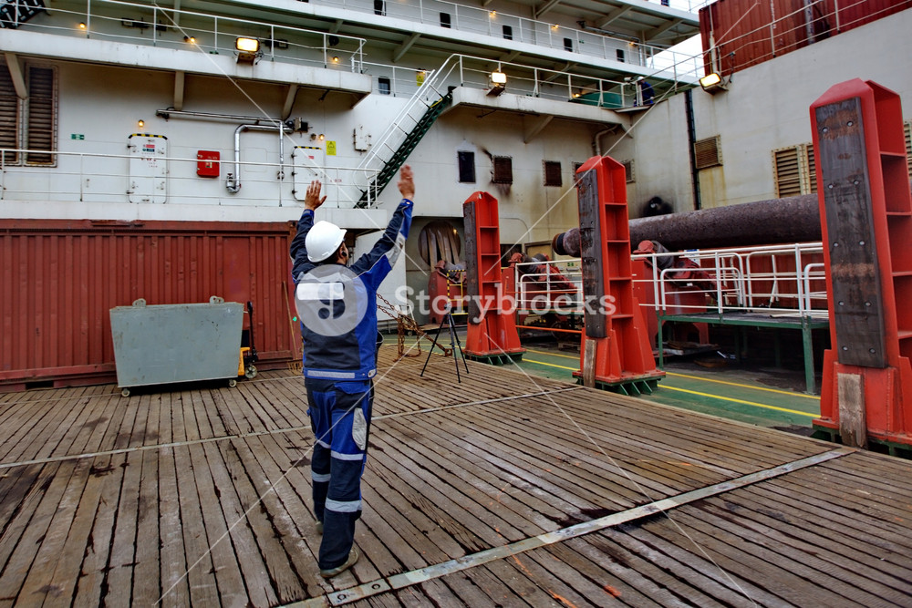 The worker shows where to put freight. deck of the pipelaying vessel.