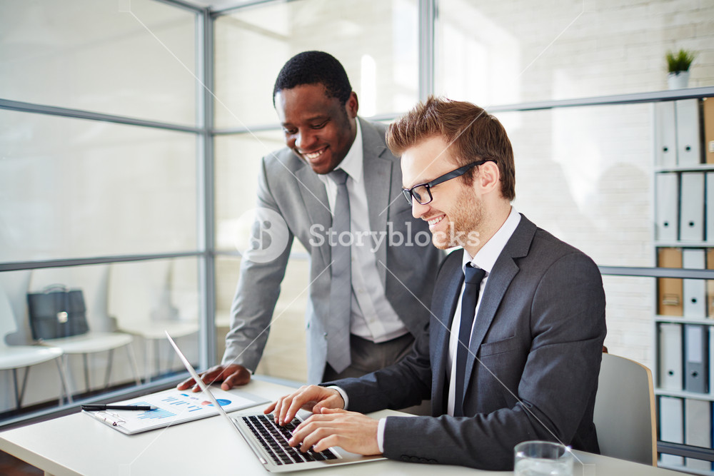 Happy Young Businessman Typing On Laptop At Workplace With His Colleague Standing Near By