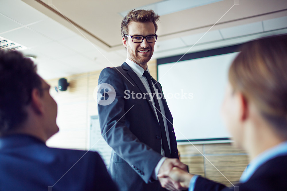 Elegant Employee In Suit And Eyeglasses Greeting Businesswoman At Conference