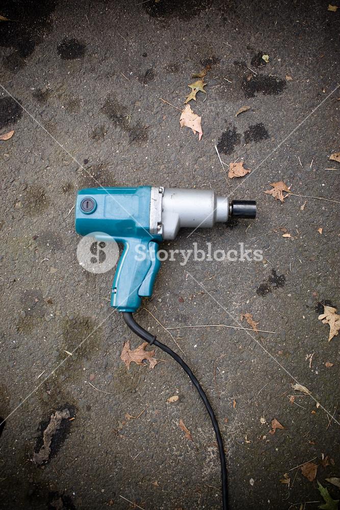 A backyard mechanics impact wrench laying on the blacktop.