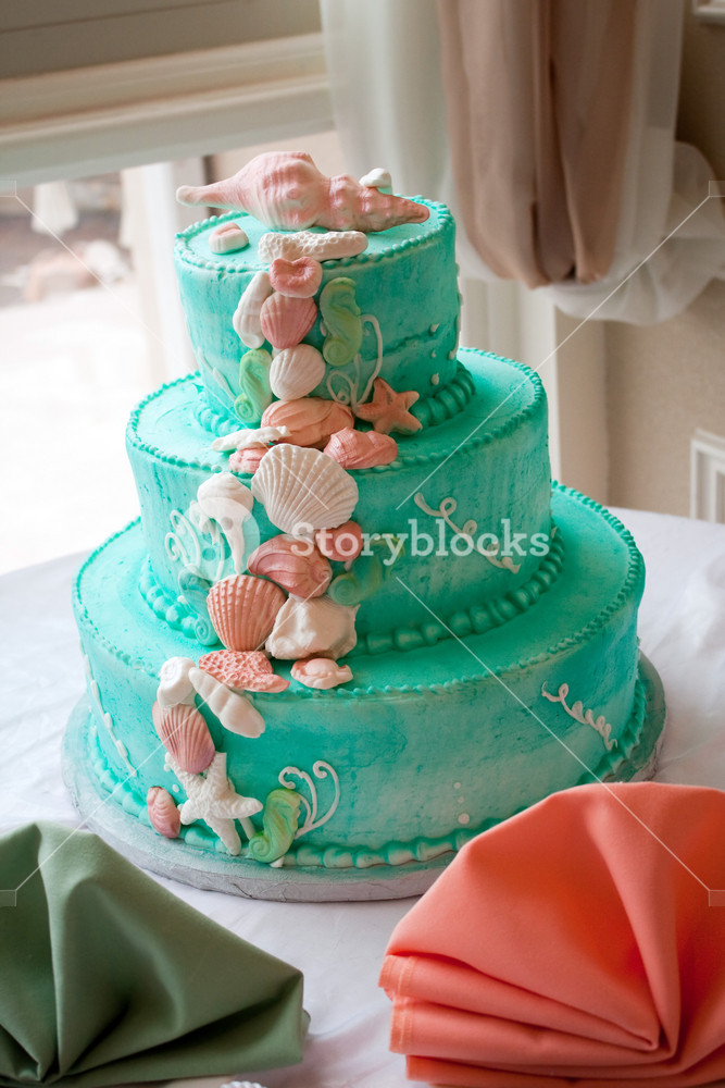 A blue beach themed wedding cake with three tiers.