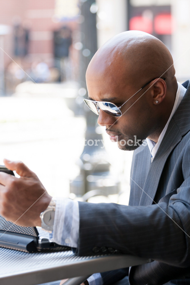 A business man in his early 30s working on his laptop or netbook computer outdoors.