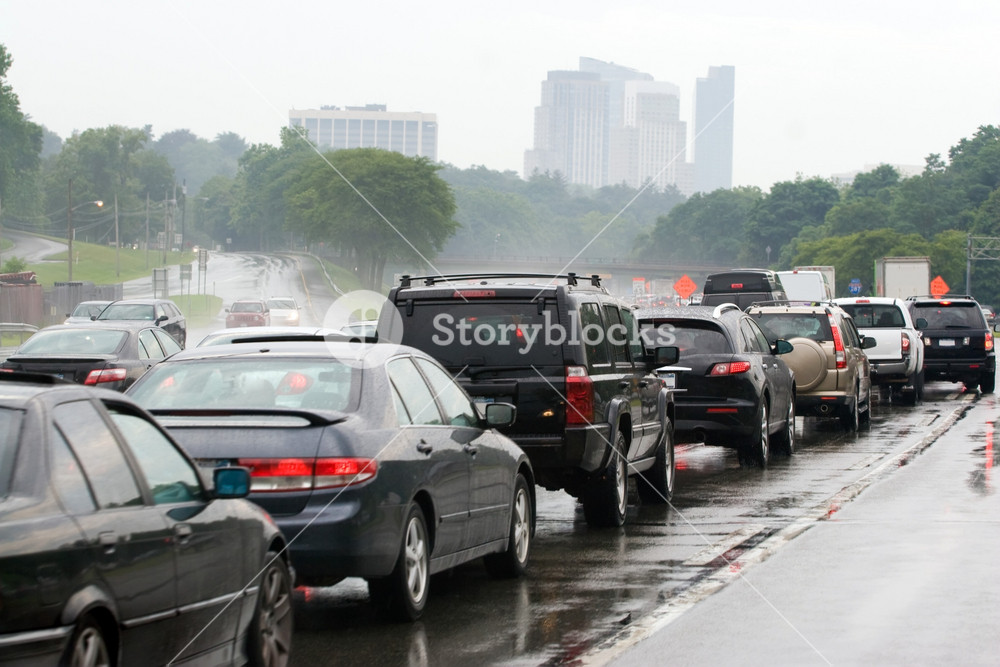 A busy congested highway during rush hour just outside the city.  Drivers impatiently wait in traffic in the bad rainy weather.