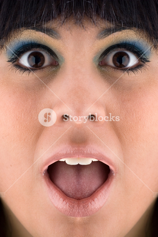 A closeup of a surprised or startled young womans face.