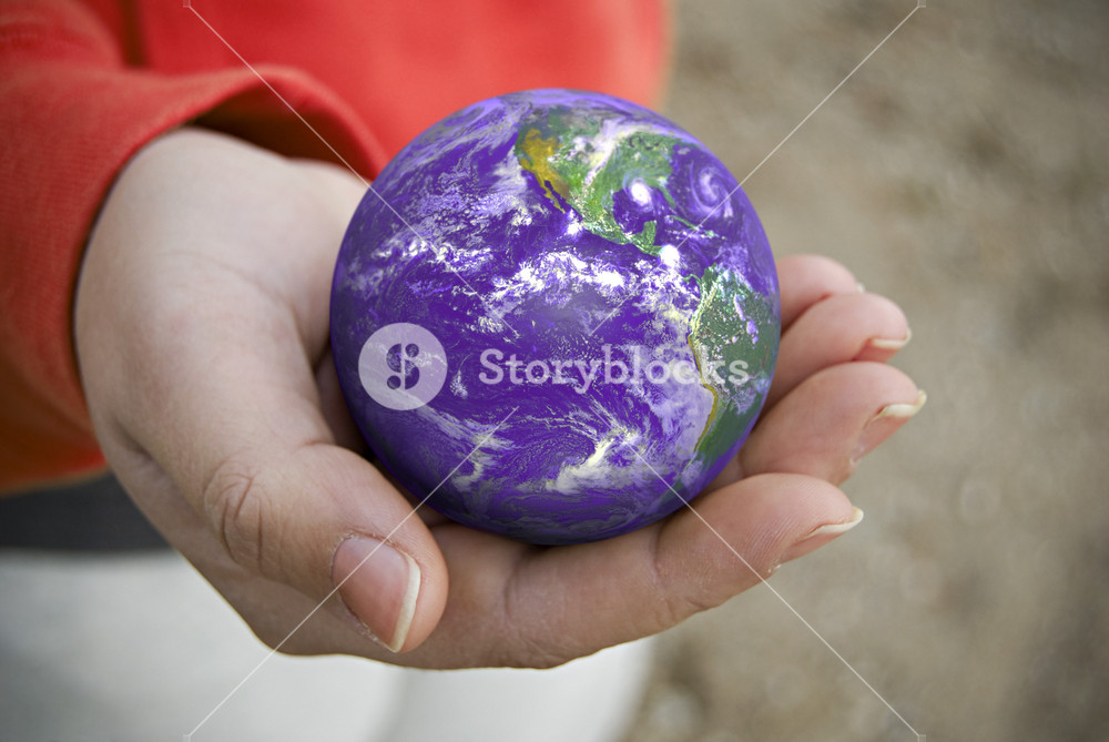 A conceptual image with the earth resting in the palm of this persons hand.