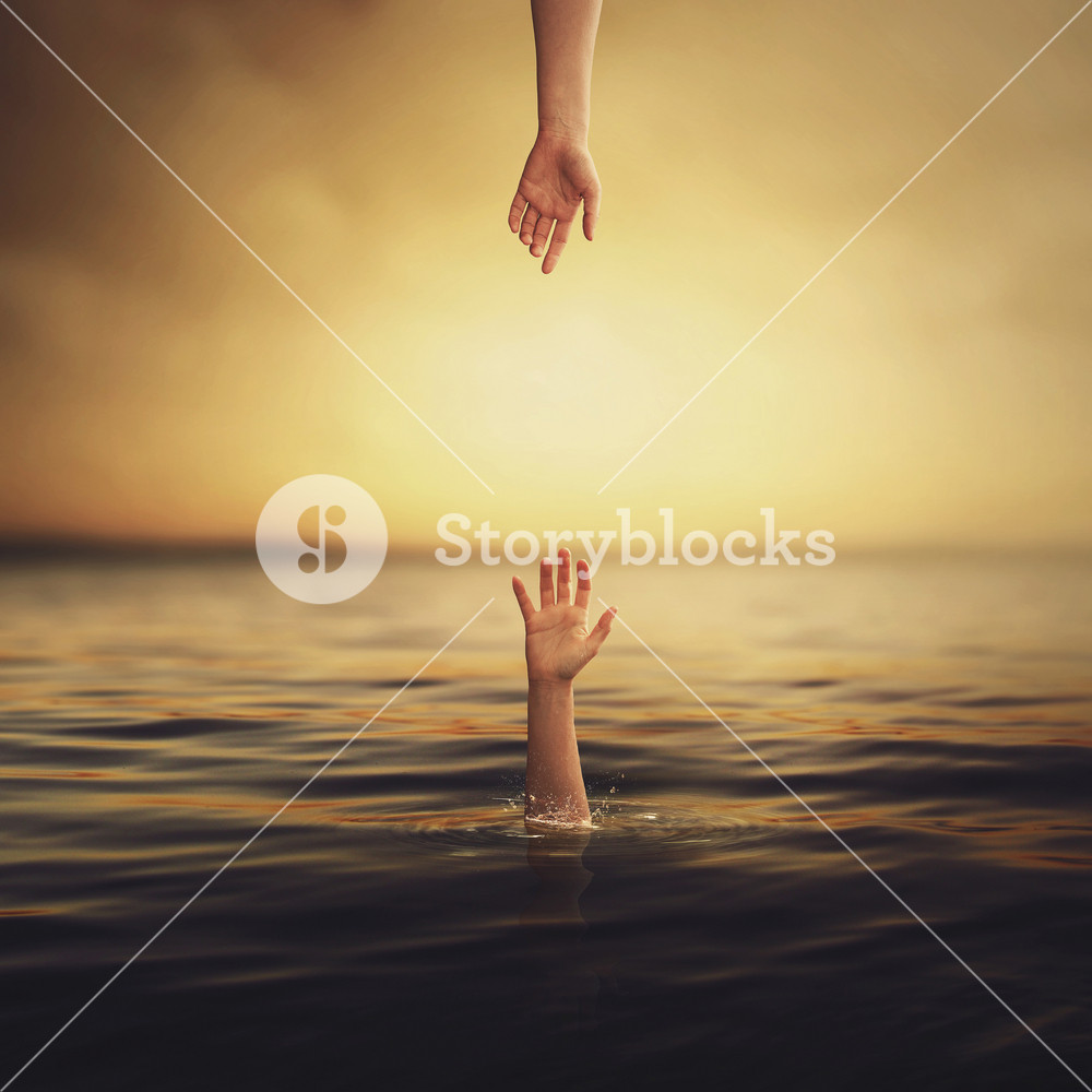 A hand comes down to save another hand from the ocean