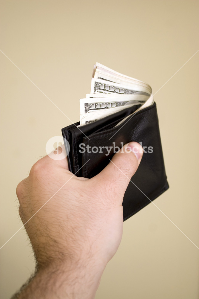 A hand holding a wallet full of cash isolated over a bold background