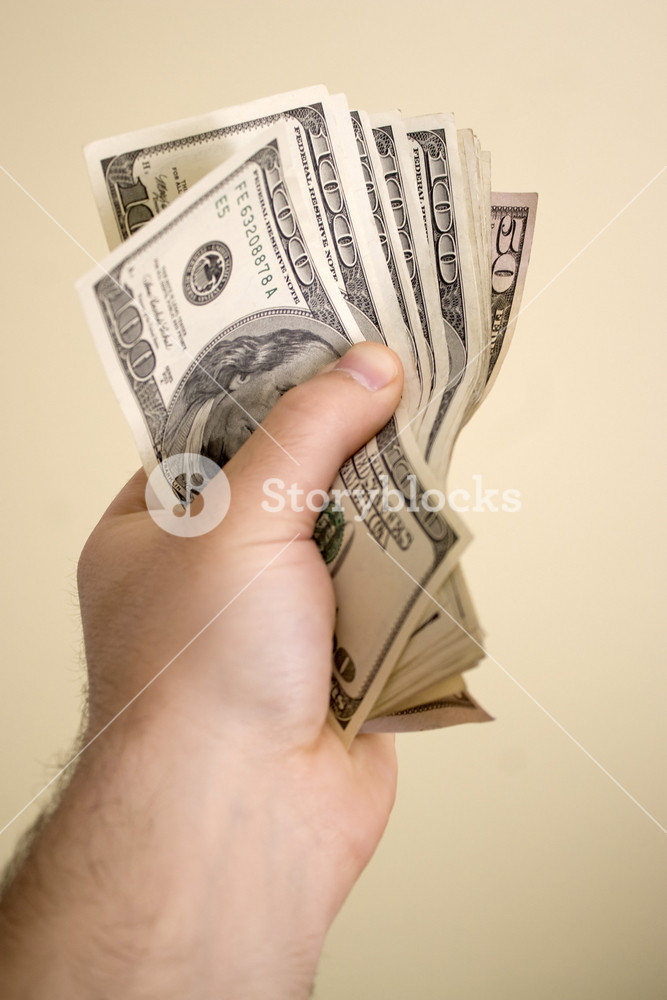 A handful of cash isolated over a solid background.