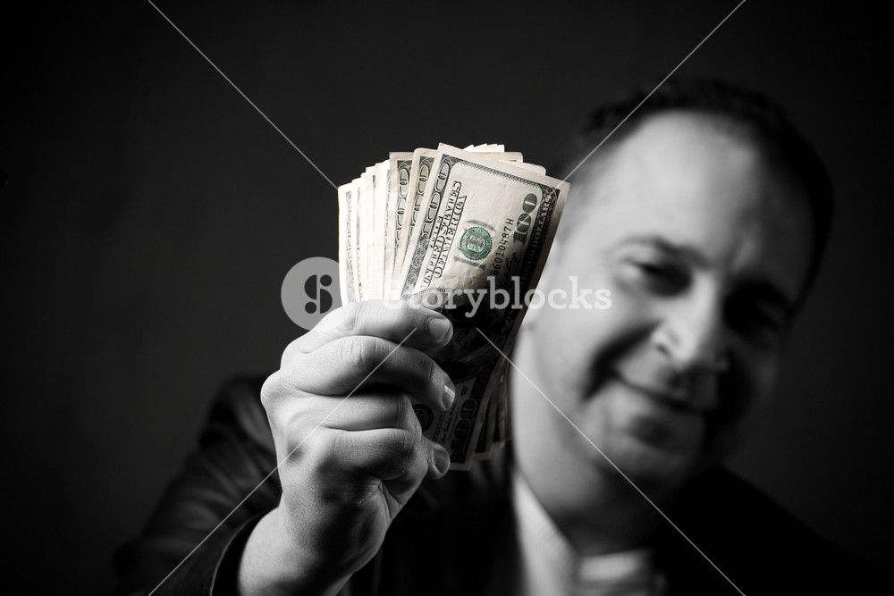 A happy man holds a handful of cash with selective color.