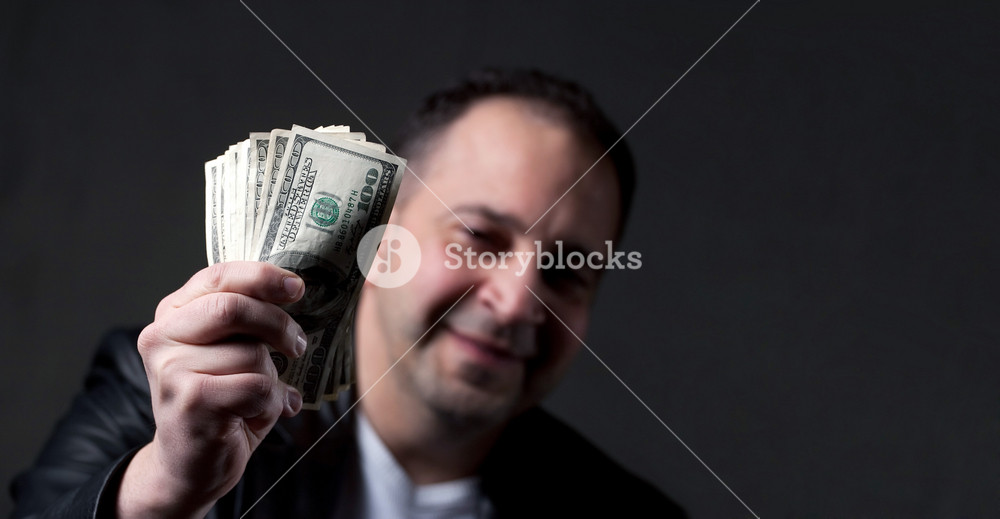 A happy middle aged man holding a handful of money with copyspace.