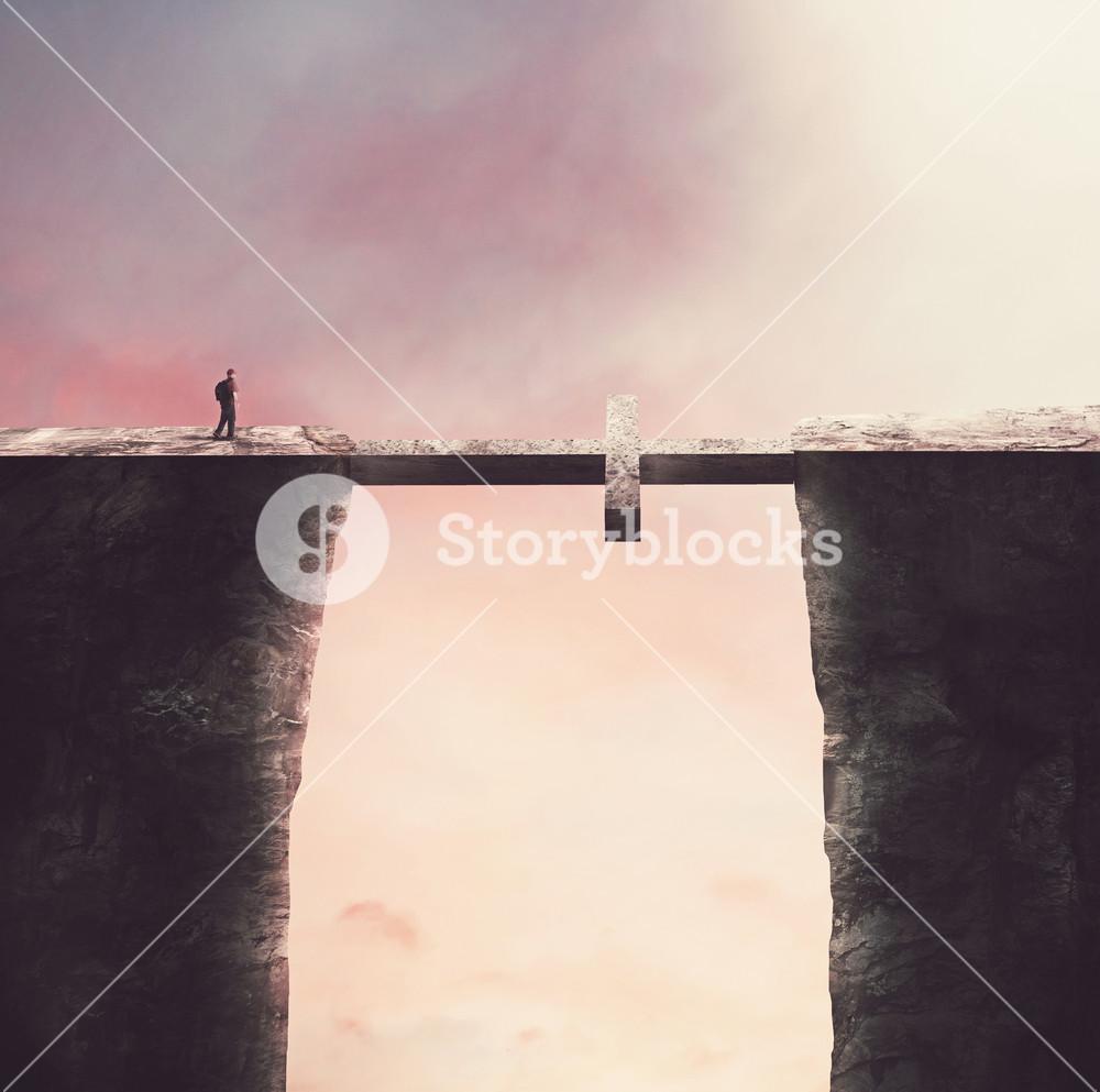 A man crosses a bridge in the shape of a cross
