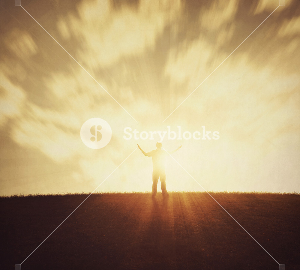 A man lifts arms in praise at sunset