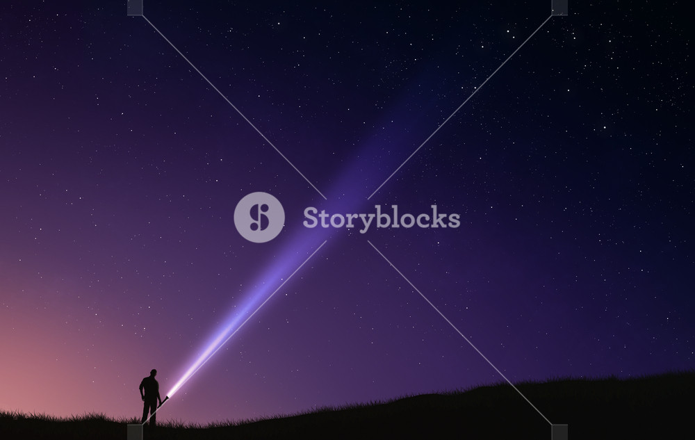 A man uses a flash light to look into the night sky.