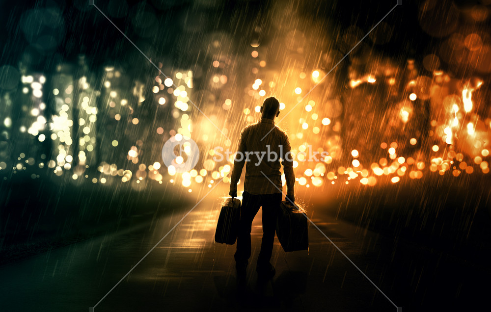 A man walking down an empty road with two suitcases towards the city.