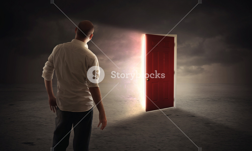 A man walks up to an open door with bright glowing lights.