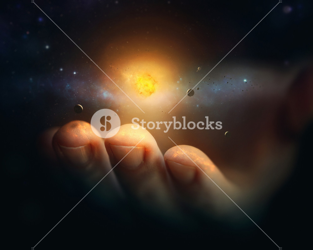 A miniature universe rests on the finger tips of a hand.
