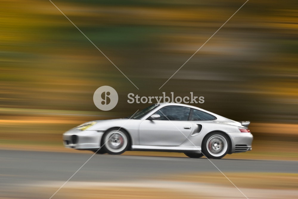 A modern sports car speeding along the road with a motion blur effect.