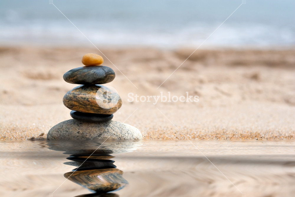 A pile of round smooth zen like stones stacked in the sand at the beach with a mirror reflection from a pool of water.