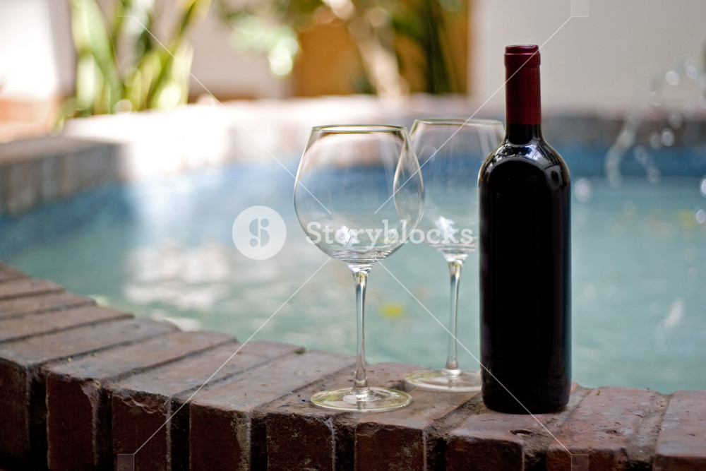 A red wine bottle and two empty glasses by the pool.