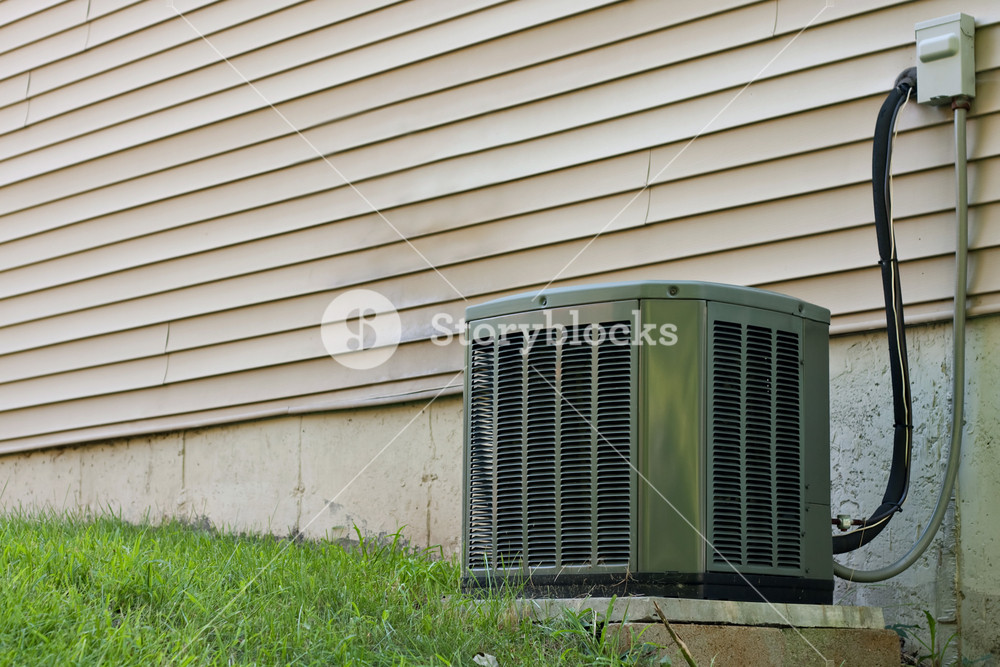 A residential central air conditioning unit sitting outside a home used for regulating the homes AC to a comfortable level.