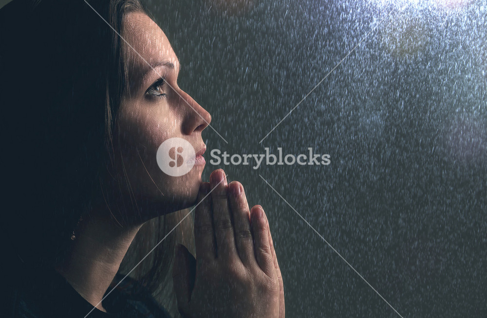 A woman holds her hands in prayer during a rain storm.