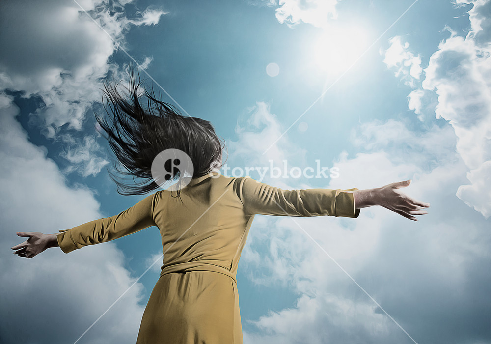 A woman in a yellow dress lifts her arms in praise