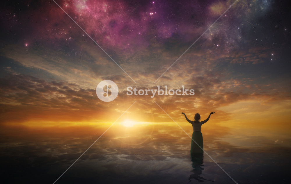 A woman lifts her arms in praise as the sun sets
