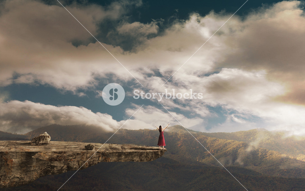 A woman on a tall cliff lifts her arms in praise