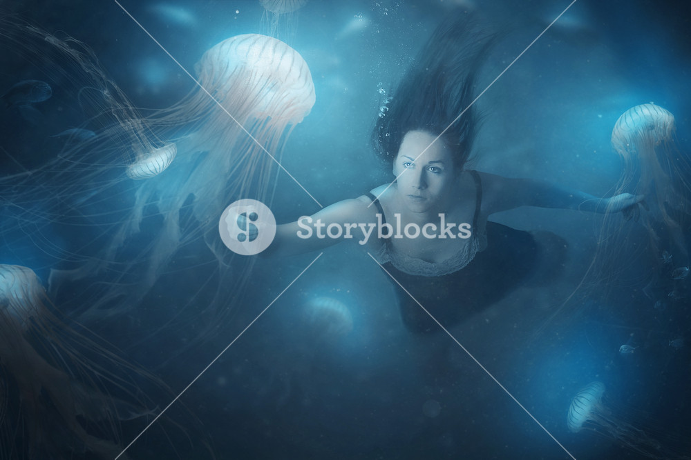 A woman swimming in the deep ocean with jelly fish