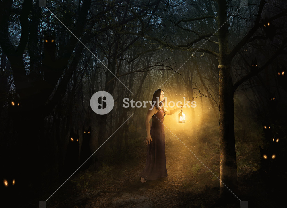 A woman walks in the forest at night with a lantern.