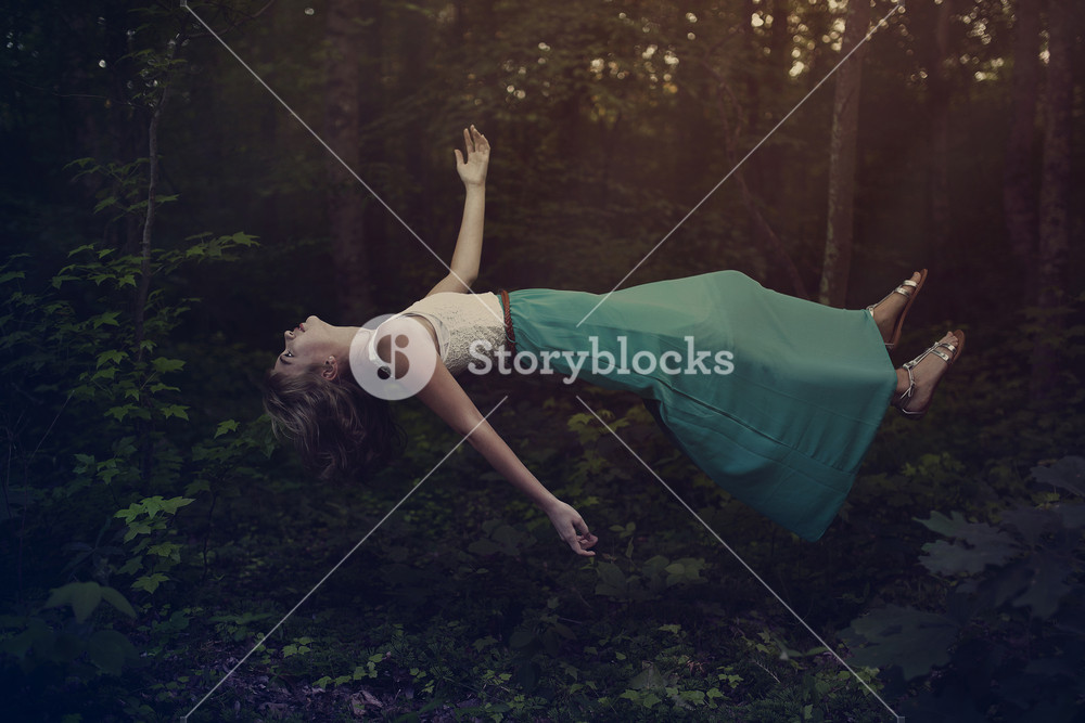 A woman with a dress is floating in the forest.