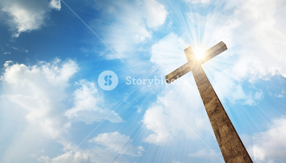 A wooden Christian cross with bright sun and clouds.