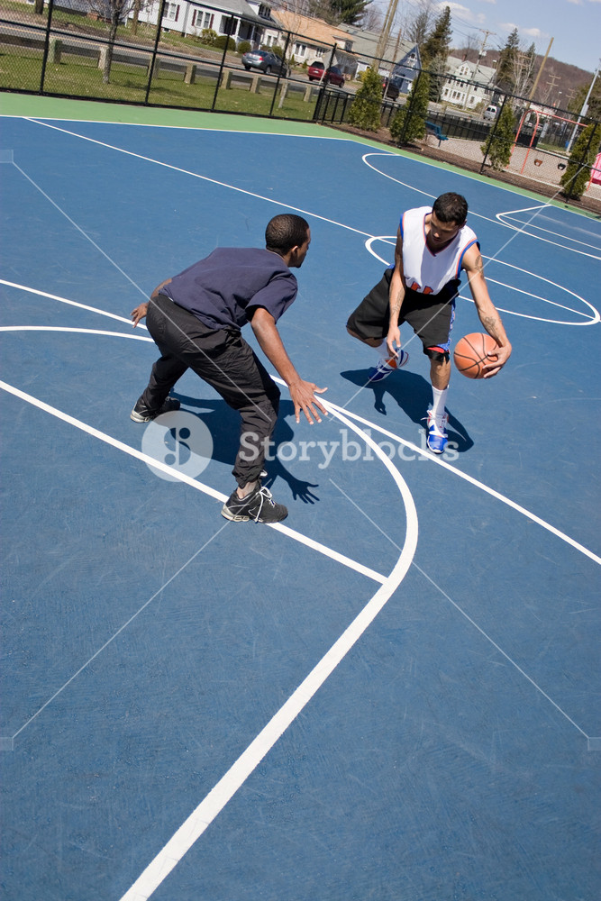 A young basketball player guards his opponent during a one on one basketball game at the park.