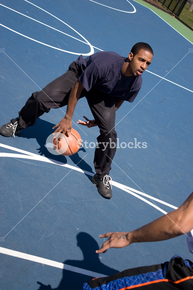 A young basketball player posts up against his opponent during a one on one basketball game.