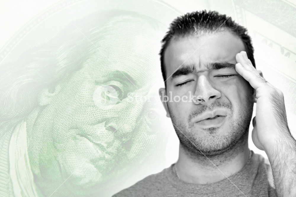 A young man holds his head in anguish as he thinks about his money problems with either debt or unemployment.
