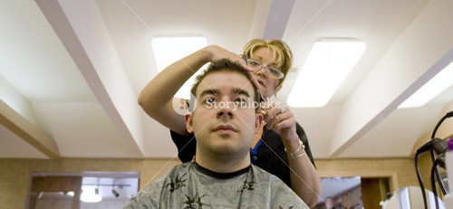 A young man is getting his hair cut by a hairdresser at the salon