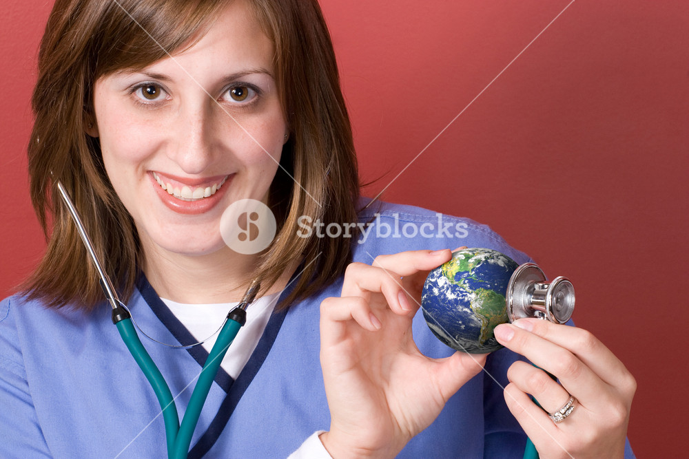 A young nurse holds a stethoscope to the earth.  This conceptual image works great for the going green movement.